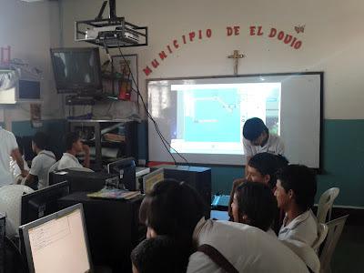 En la imagen se observa una proyección del vídeo beam y los estudiantes haciendo circuitos en el simulador