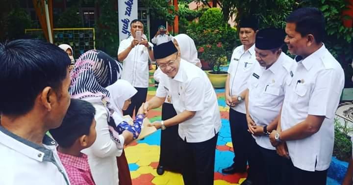 Bupati Sarolangun Menyerahkan Bantuan seragam sekolah Siswa Kurang Mampu