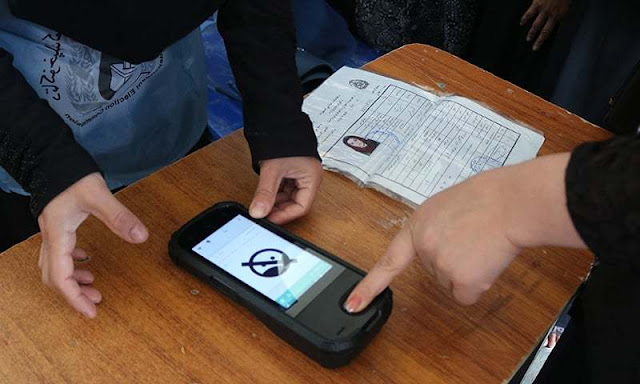 Image Attribute: An Afghan Independent Election Commission (IEC) official (L) scans a voter's finger / Source: Reuters
