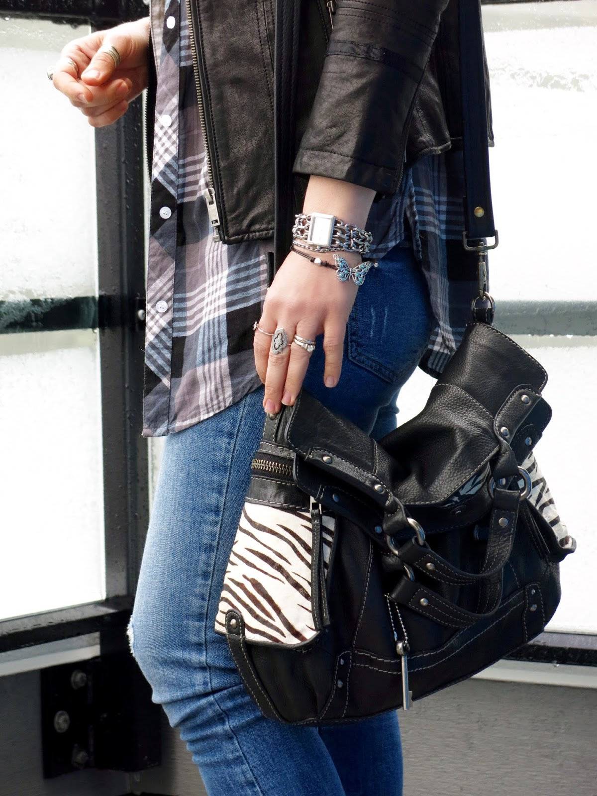 moto jacket, plaid shirt, skinny jeans, and Fossil bag