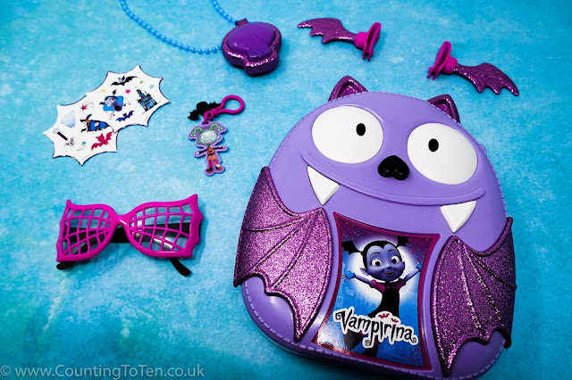 The Vampirina bat shaped backpact surrounded by the items from the set: stickers, sunglasses, necklace, bag clip and hair clips