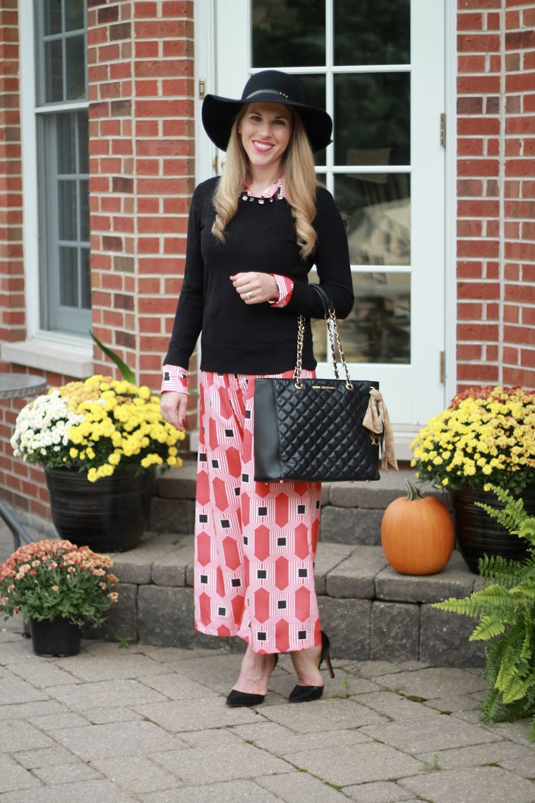 red geometric print jumpsuit, black floppy hat, black quilted leather tote, black embellished sweater