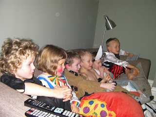 kids lined up on sofa to watch tv