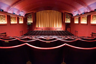Before the audience arrives, the cinema is quiet, the curtains over the screen are uplit and outside the corn is popping Take your seats the show is about to start.