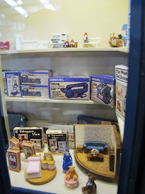 Various dolls' house-related items displayed in the window of a one-twelfth scale toy shop.