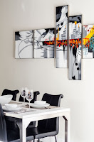 Table with black chairs, empty glasses and plates. Wall art with colors.