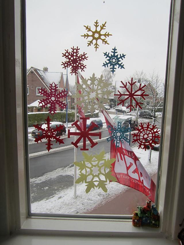 kerstboom op raam papieren sneeuwvlokken