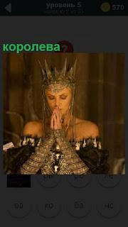 Женщина с короной на голове, королева сложила руки перед собой