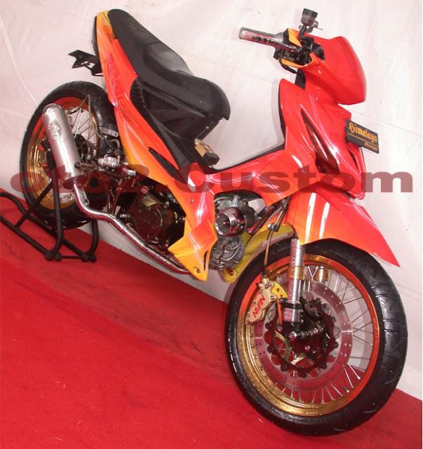 Foto Modifikasi Honda Revo dengan modif Racing Road Race didominasi warna yang mencolok yakni oranye dan sedikit warna kuning dibagian bawah bodi motor untuk belakang jok dibuat meruncing tak lupa jari-jari dibuat rapat lurus untuk pada bagian velg diwarna oranye kesekujur lingkar pelek