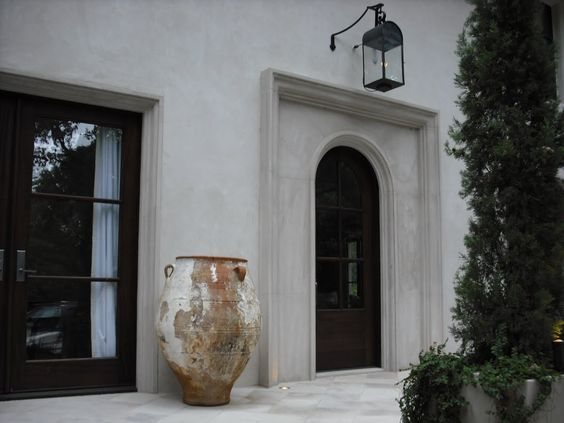 Antique French urn at entrance of grand stucco home with black trim and accents.