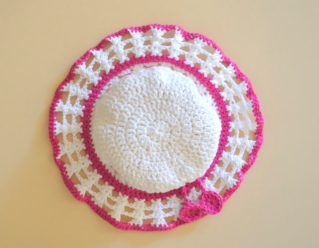 Above-view of the hat. The crown is white with pink borders where the crown meets the brim and at the end of the brim. The body of the brim is a lacy crossed stitch pattern.  The two discs that decorate the ends of the drawstring can also be seen.