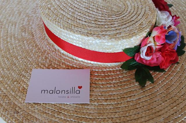 Detalle de la pamela de paja trenzada con cinta roja, flores y tarjeta malonsilla tocados & artesanía