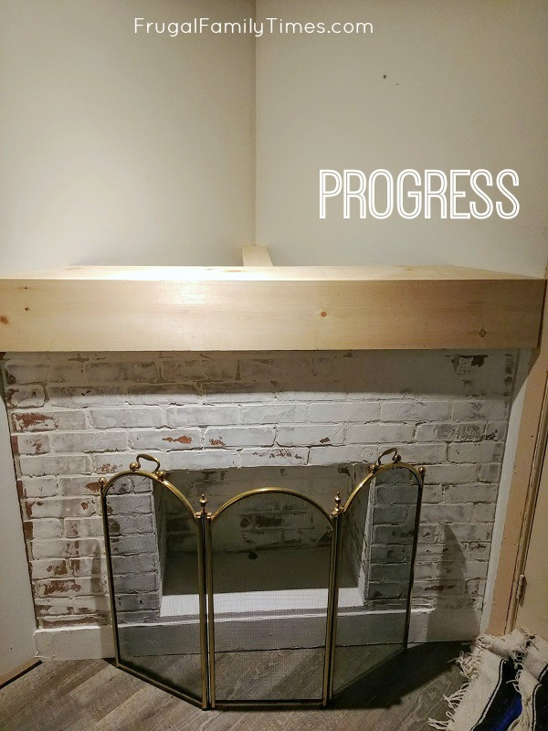 corner brick fireplace with wood mantle