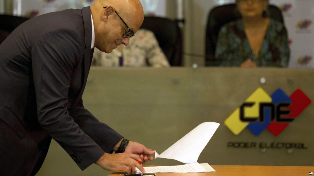 Ministro de Comunicaciones, Jorge Rodríguez, firma en nombre del gobierno un acuerdo para postergar las elecciones / AP