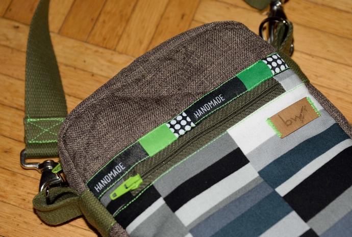 Nahaufnahme der Details auf der Vorderseite: Reißverschlussfach mit kontrastfarbenem Schieber, Handmade-Webband, mein Label und Gurtlösung