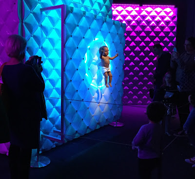 Pic of brightly-lit baby animatronic with visitors standing back from it