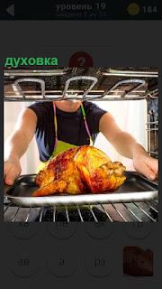 Повар на подносе укладывает в духовку курицу для приготовления