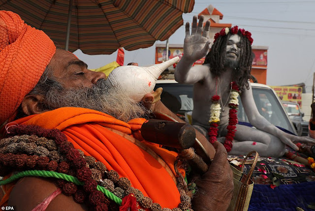 Hindu Holy man blows the Shank or conch shell as an Indian Naga Sadhu or naked holy man gives blessings outside his tent