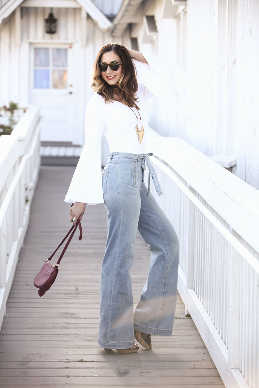 Amy West in wide leg jeans and a white tee with bell sleeves
