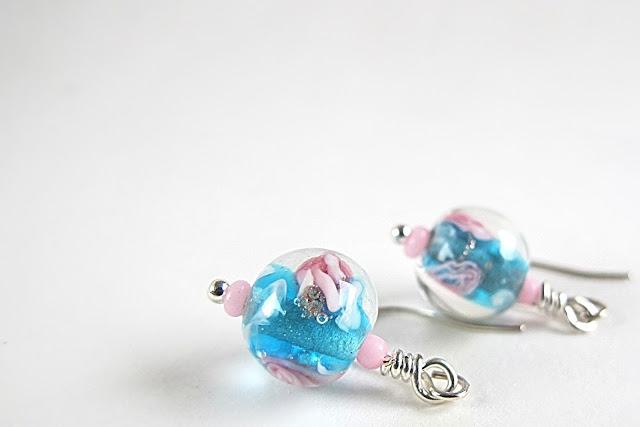 kleine blauwe glazen bloemenkraaltjes aan minihaakjes ( geen zilver )  totale lengte : 2,5 cm
