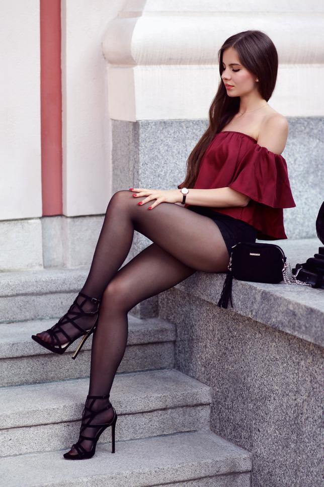 Bordowy top, szorty z wysokim stanem, czarne rajstopy i sandały na szpilce