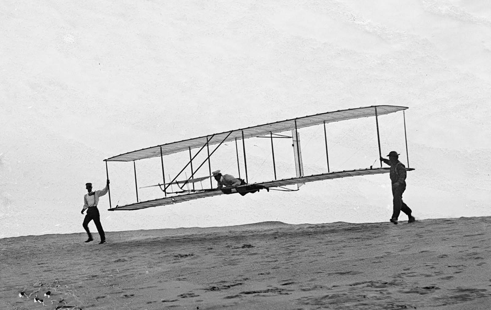 Start of a glide; Wilbur in motion at left holding one end of glider (rebuilt with single vertical rudder), Orville lying prone in machine, and Dan Tate at right, in Kitty Hawk, North Carolina, on October 10, 1902.