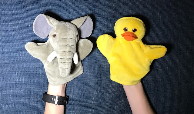 A small elephant hand puppet and a bright yellow duck puppet on the end of arms on a blue fabric background