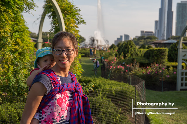 [Image of a smiling tan skin bespectacled Asian woman wearing a toddler on her back in a red and blue checked woven wrap carrier. They're in a green garden. In the background is a large fountain and several skyscrapers.]