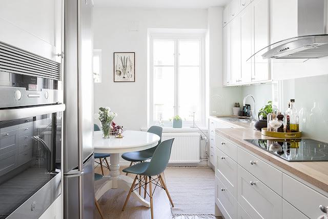 biała kuchnia, kuchnia w stylu skandynawskim, okrągły stół IKEA, krzesła enzo, niebieskie krzesła