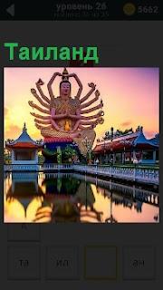 Изображение в Таиланде будды с 18 руками. На переднем плане водоем и рядом здания в национальном стиле