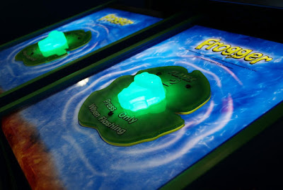Green illuminated button on a large ICE Frogger redemption game. One press to play.
