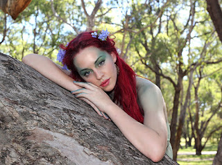 woman resting on rock, red hair, trees, photo manipulation