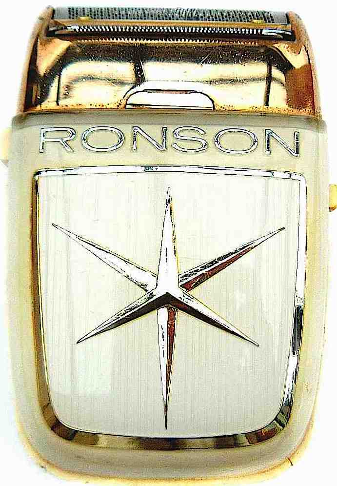 color photograph close-up of a 1950s Ronson men's shaver in gold metal with starburst