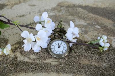 Reloj antiguo en la playa  con flores
