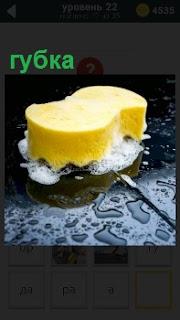 Осуществляется уборка желтой губкой с пеной чистящегося средства грязной поверхности