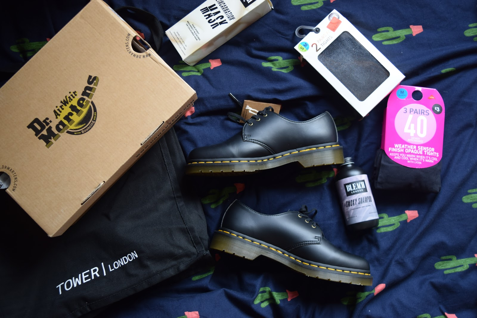 flatlay of Dr Martens 1461 shoes, tights and Bleach London products