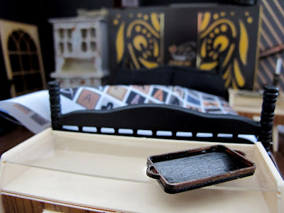 Modern dolls' house miniature room set up in dark shades of black, brown and cream.