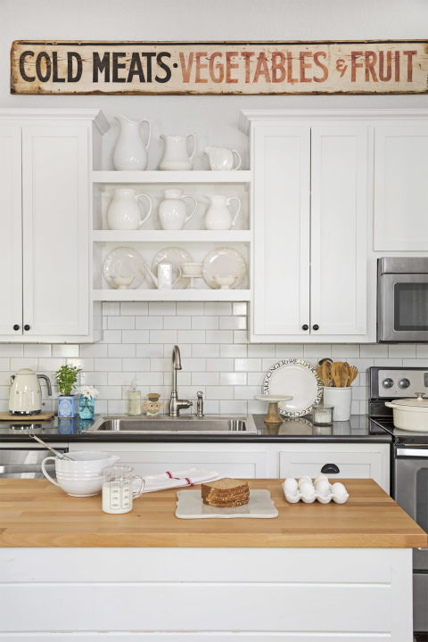 Charming cottage style in a farmhouse kitchen with subway tile, white cabinets, and vintage wood sign. #kitchen #cottage #farmhouse #vintagestyle #subwaytile