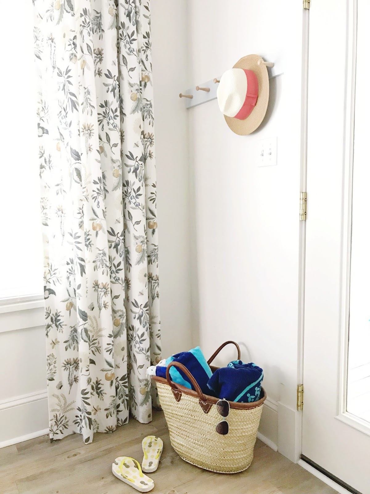 diy shaker peg rail, straw hat, country floral curtains, beach bag