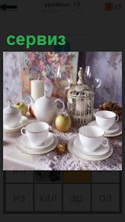 На столе стоят чашки, чайник, отдельные предметы из фарфорового сервиза