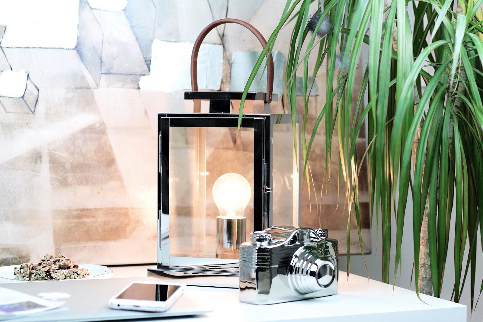 Stylish desk setup with chrome lantern