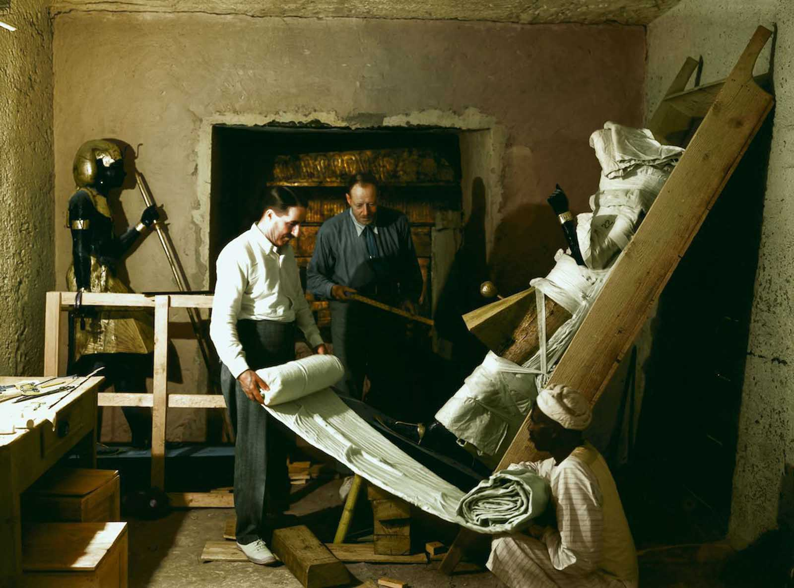 Howard Carter, Arthur Callender and an Egyptian worker wrap one of the sentinel statues for transport.