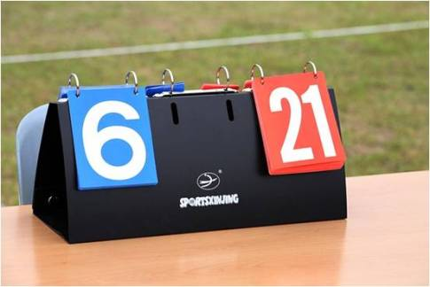 A sports scoreboard on a wooden table outdoors
