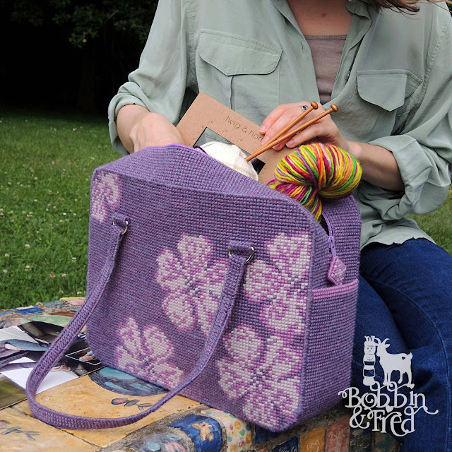 Woman sat in park with craft project bag