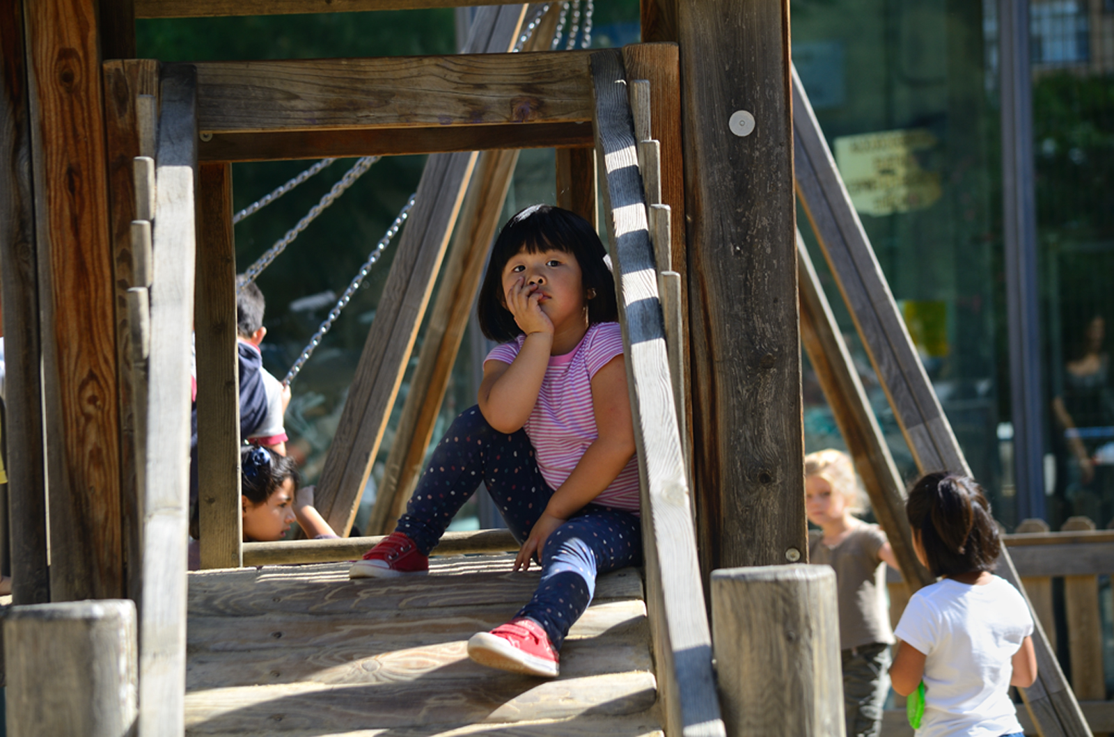 Chinese girl in wooden playground framework