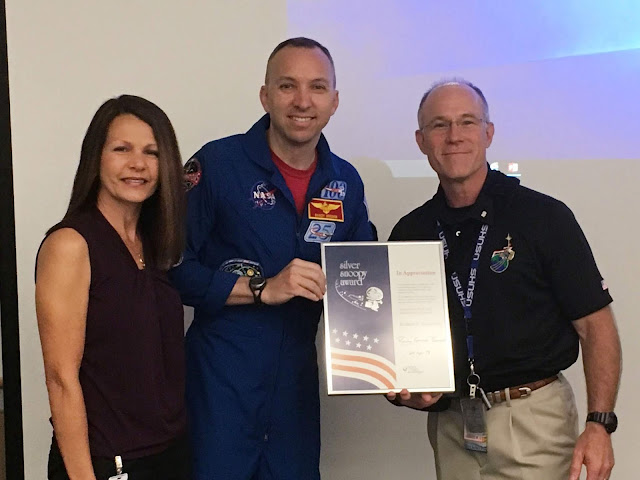 A man in a astronaut flight suit presents a certificate to another man