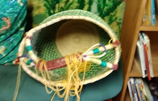 Multi-colored basket turned on its side with yarn spilling out of it