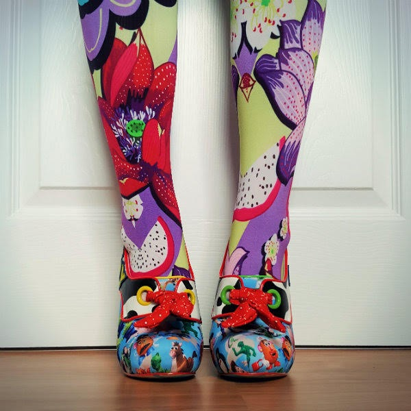 legs facing forward in bright floral tights with Toy Story patterned shoes