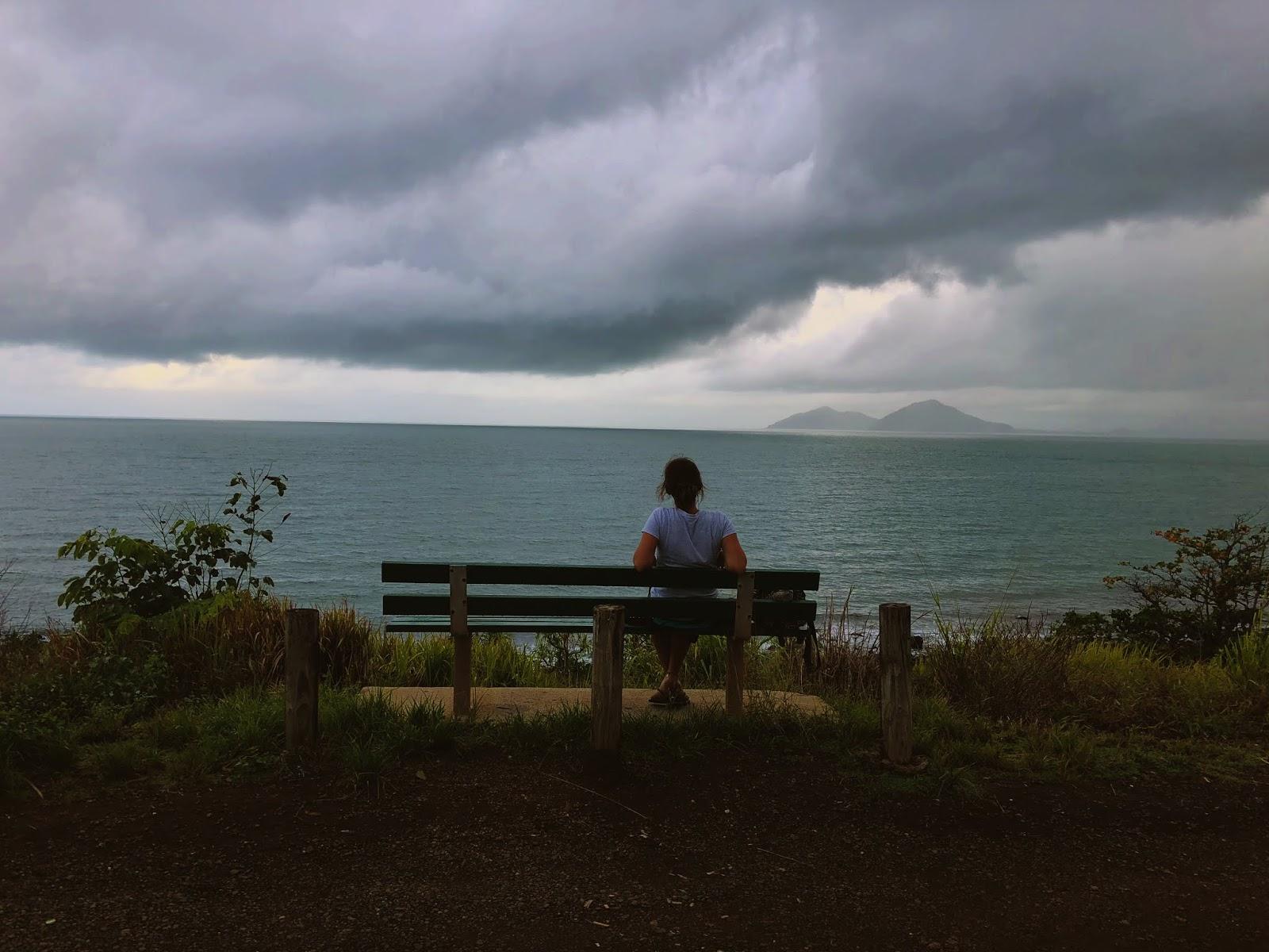 Punkt widokowy w australijskim miasteczku Mission Beach. Widok na małą wyspę znajdującą się w oddali na Morzu Koralowym. Na środku stoi ławka, na której siedzi podróżniczka i wpatruje się w horyzont.