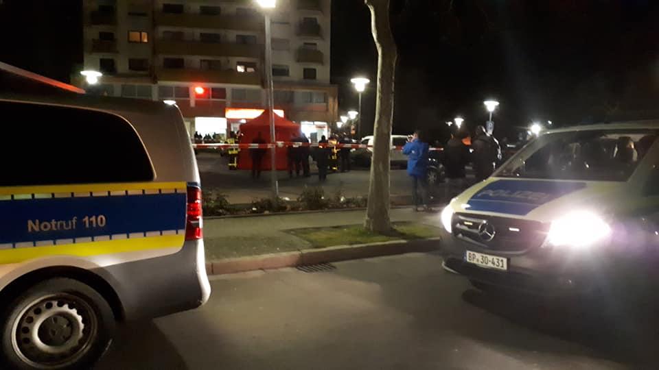 Policijas mašīnas un izmeklētāji ap uzbrukuma vietu